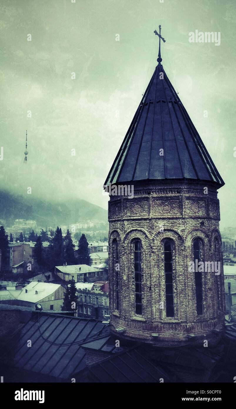 Georgian Orthodox Church Tower with crucifix on domed roof. In background through the mist of an overcast day The - Stock Image