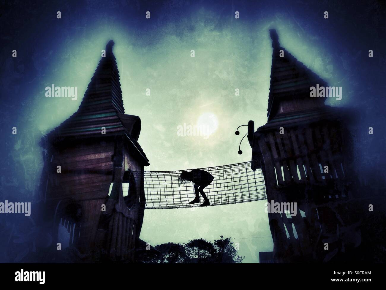 Girl crossing bridge between two fairytale castle towers on playground apparatus - Stock Image