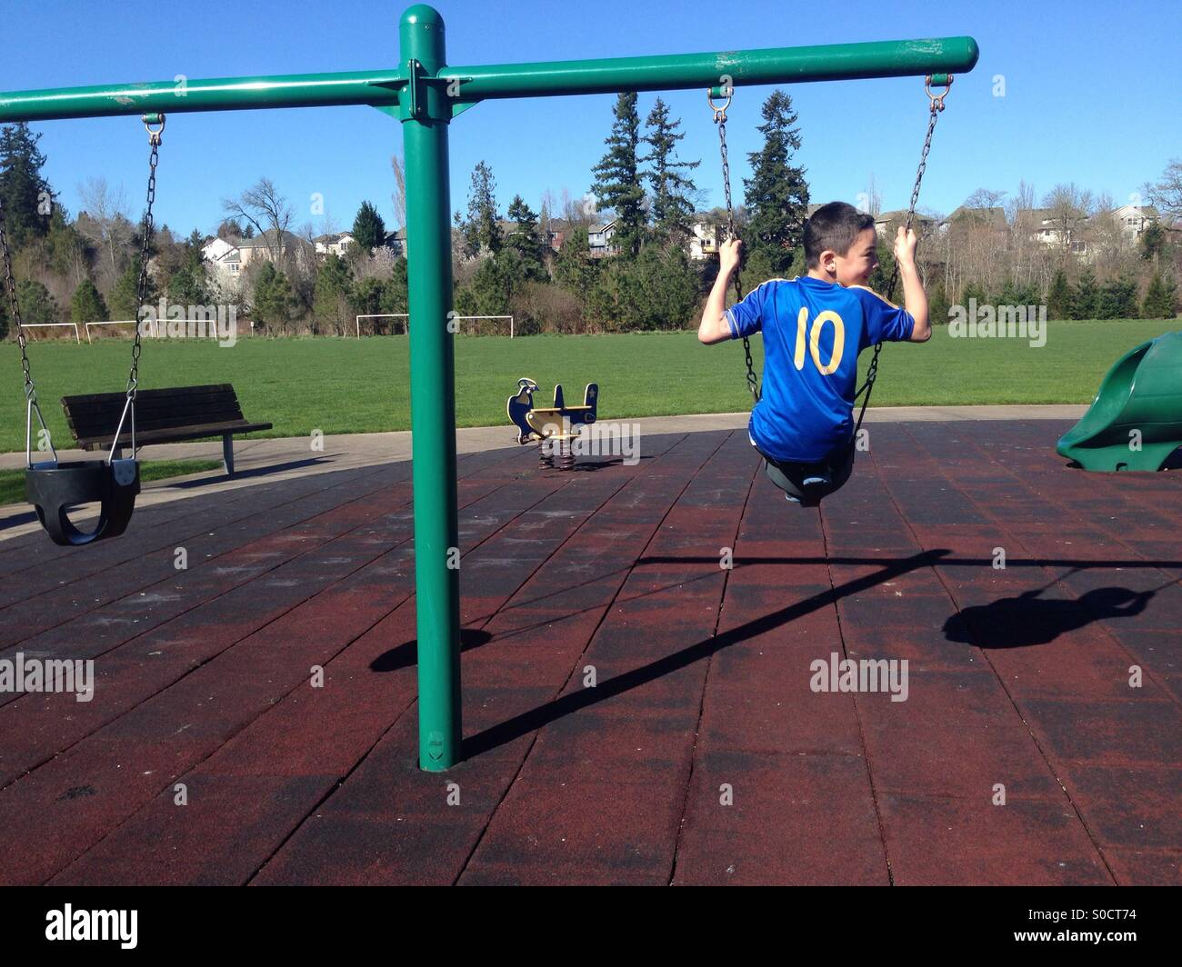 Boy on swing on playground at park - Stock Image