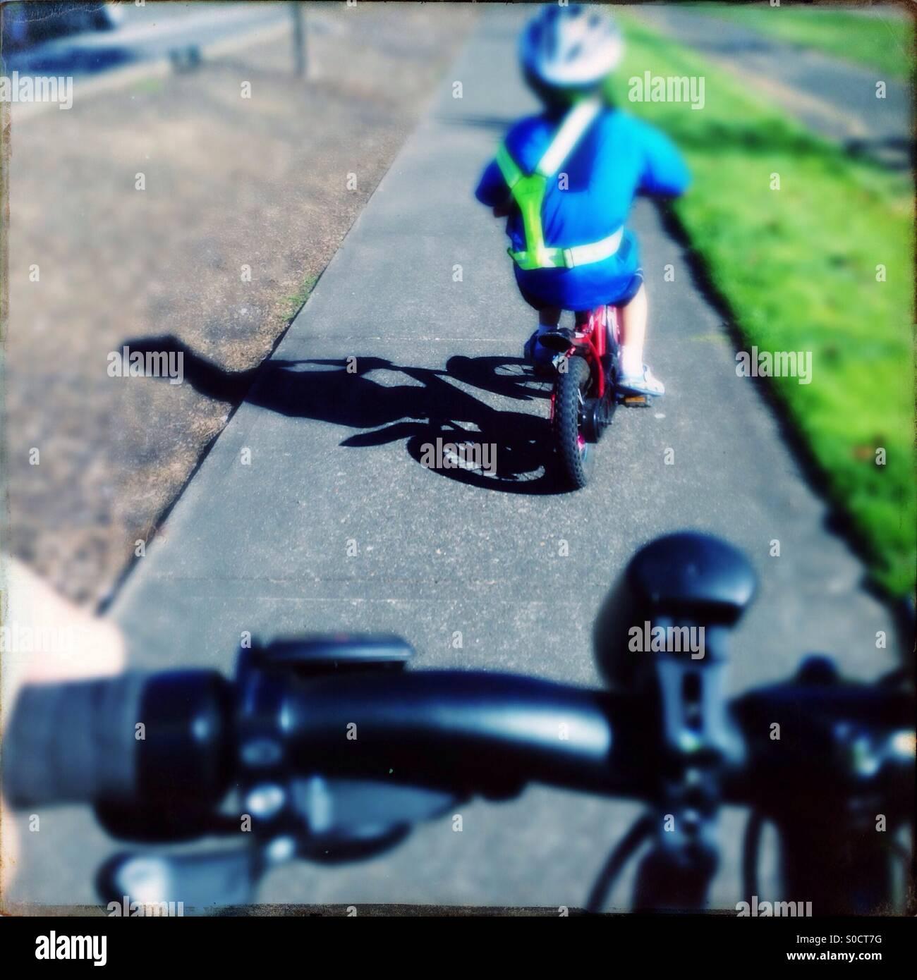 Child riding bicycle sidewalk wearing safety vest - Stock Image