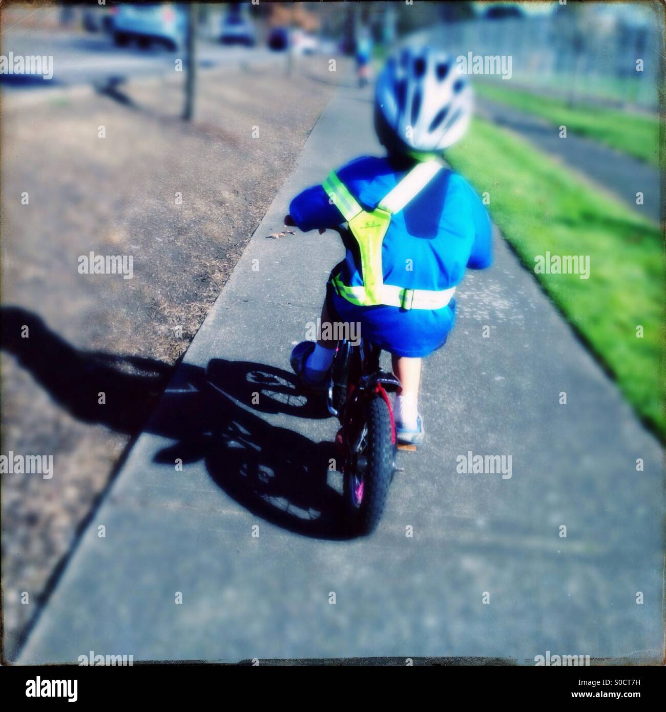 Child riding bicycle on sidewalk wearing reflective safety vest and bike helmet - Stock Image