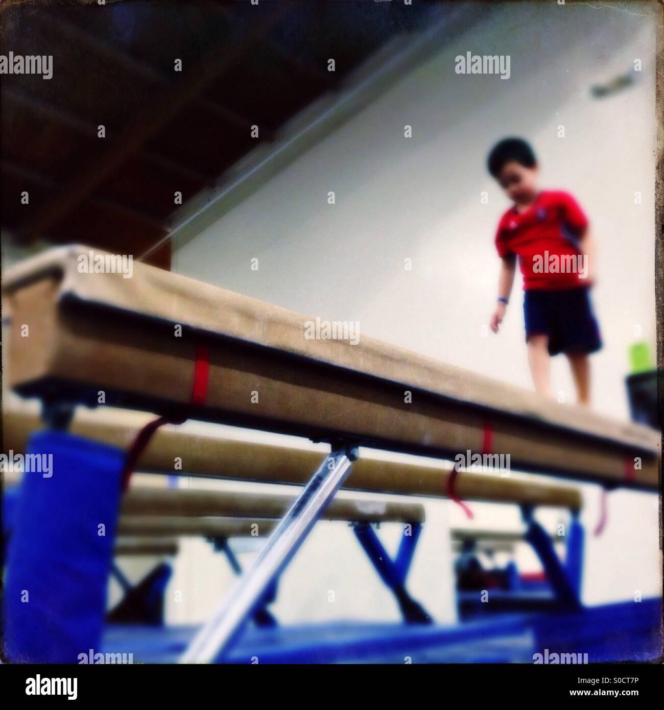 Boy on gymnastics balance beam - Stock Image