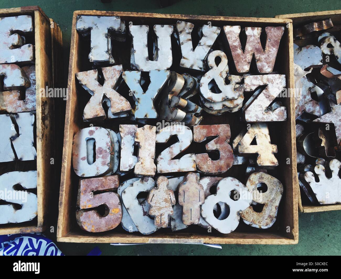 Metal letters, numbers and figures are for sale at a flea market. - Stock Image