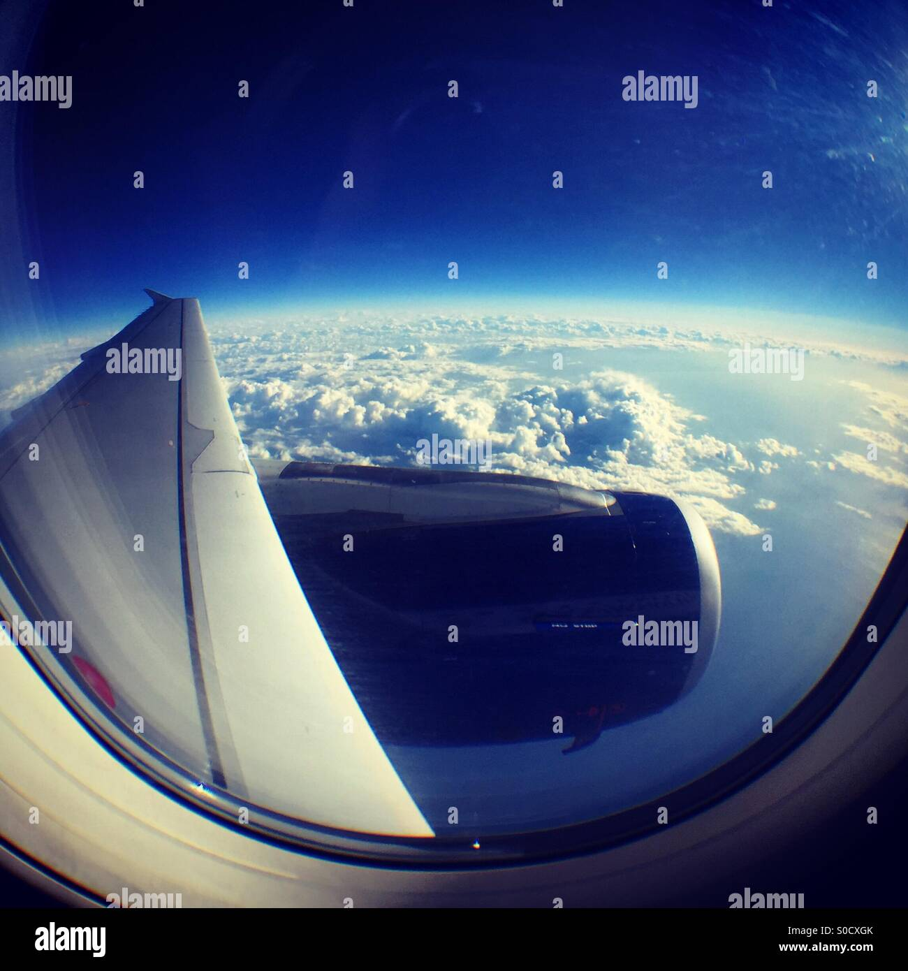 Looking out over the wing of a plane at the curvature of the earth - Stock Image
