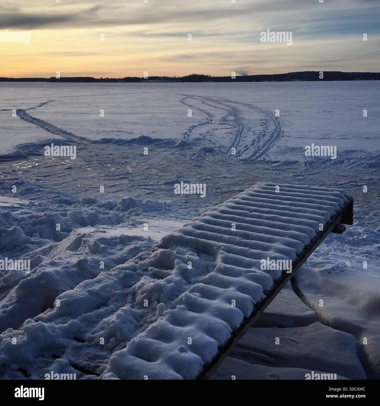 A home made ice rink, a pier and ski tracks at sunset at an idyllic Arctic frozen lake in winter in Scandinavia - Stock Image