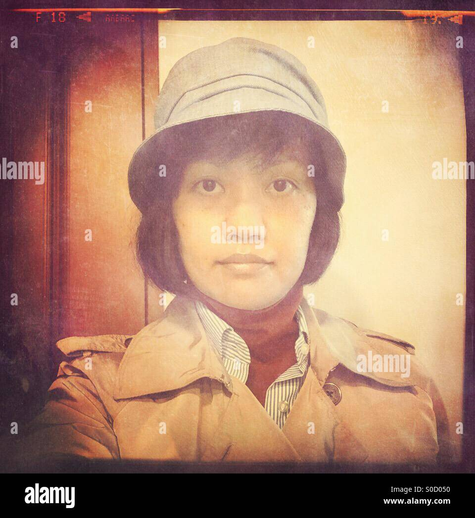 Asian woman selfie, with short bob hair, tan trench coat, red turtleneck, blue striped shirt and hat. Vintage film - Stock Image