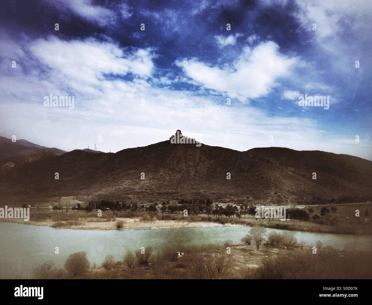 Jvari Monastery sitting on a distant hillside across the meeting point of the Mtkvari and Aragvi rivers. Landscape - Stock Image