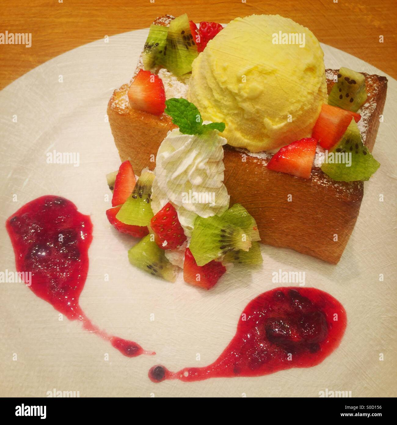 Honey toast with vanilla ice cream, sliced kiwi and strawberries, whipped cream and cranberry sauce. Vintage painterlyStock Photo