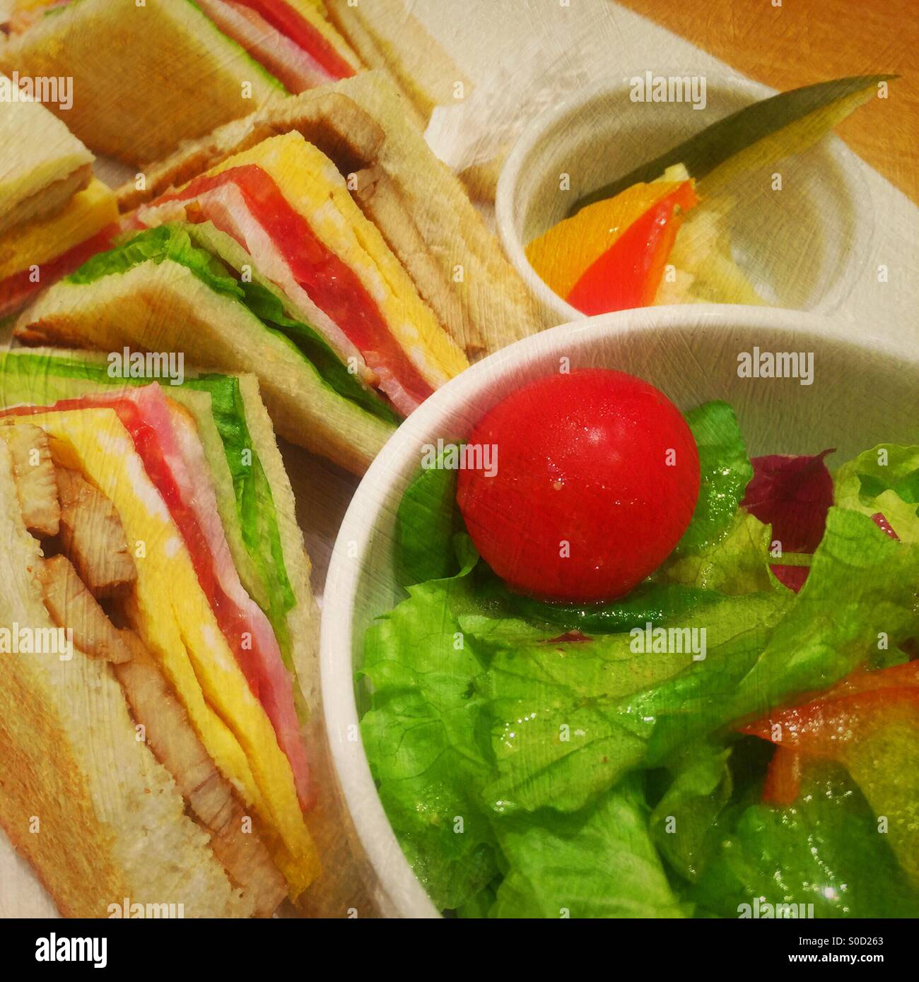 Delicious sandwiches with chicken, egg, tomatoes, lettuce and ham with side serving of pickled vegetables and greenStock Photo