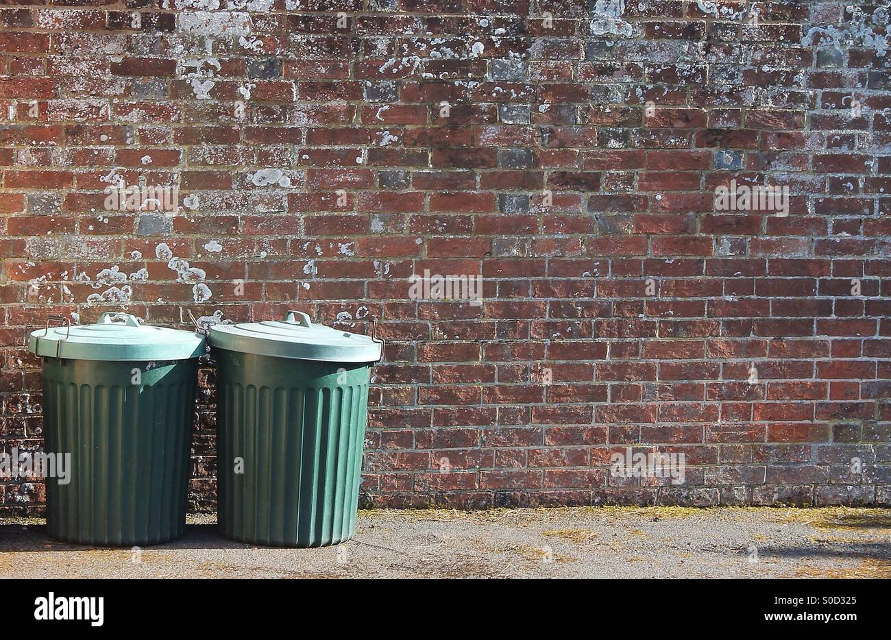 Trash can rubbish dustbins garbage can by brick wall copy space background Stock Photo