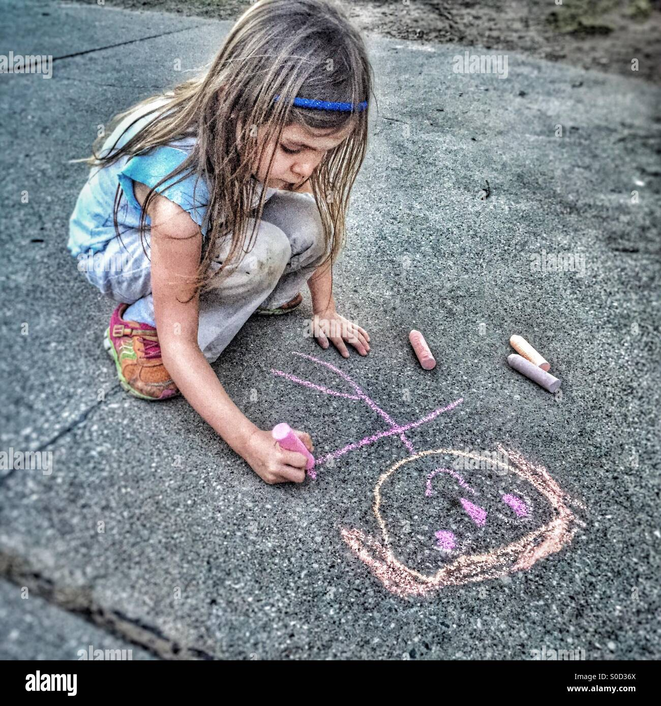 Girl drawing figures with chalk on a driveway - Stock Image