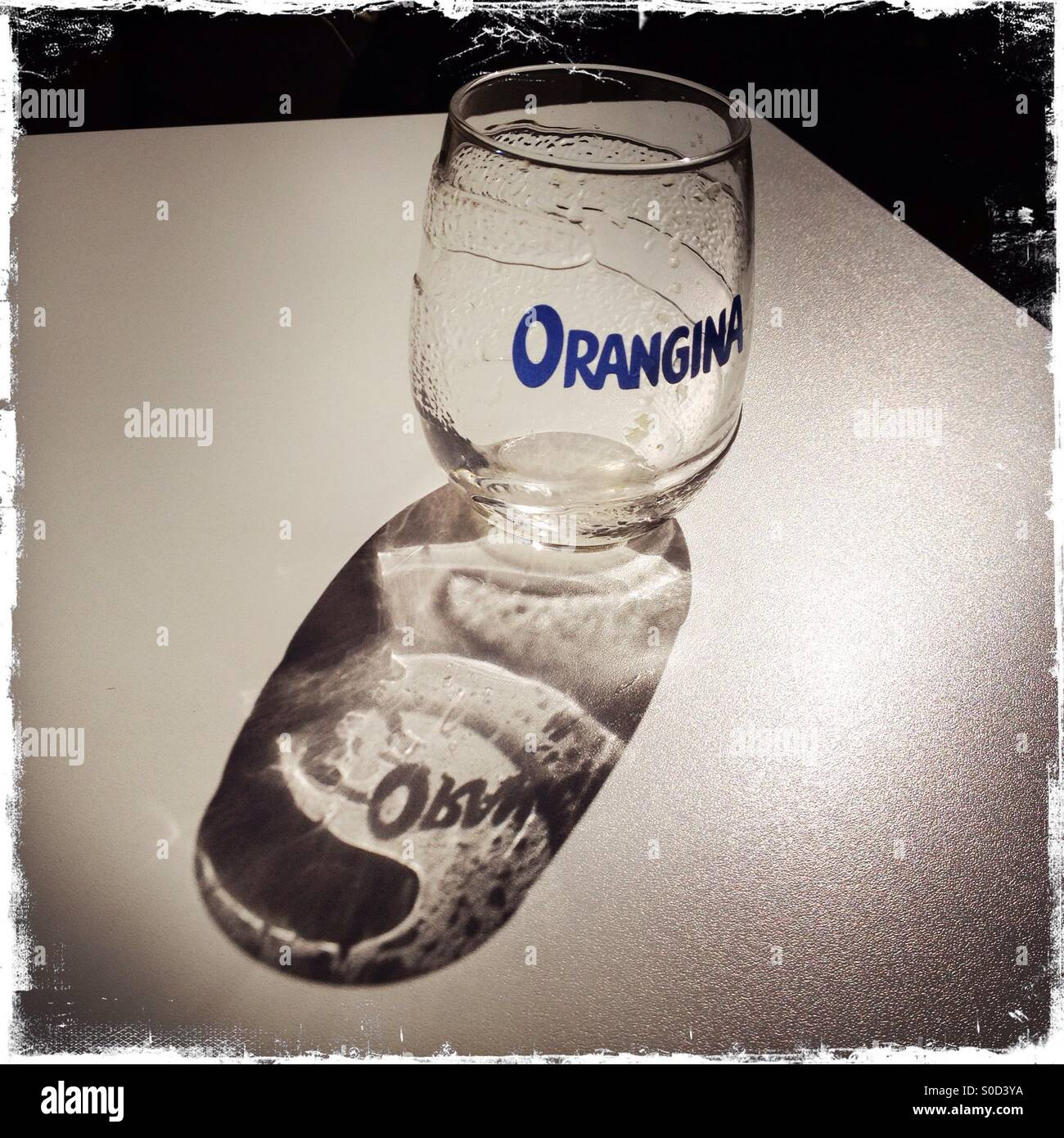 Shadow of an empty glass of Orangina on a French cafe table in the sun. - Stock Image