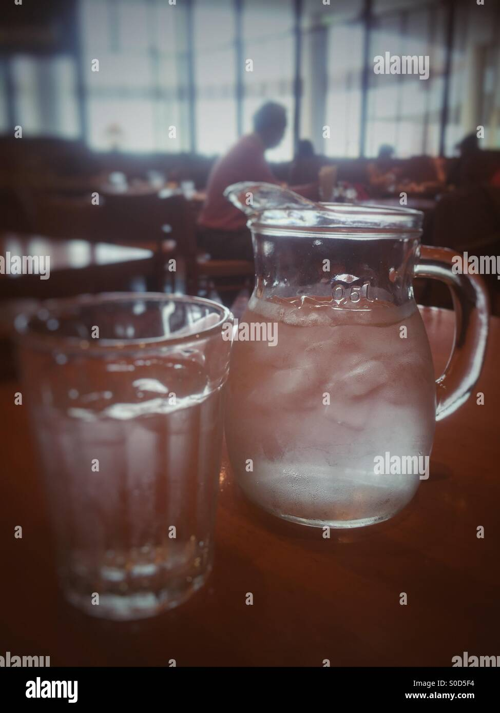 Pitcher and glass of ice water in a restaurant. Retro, faded look. Stock Photo