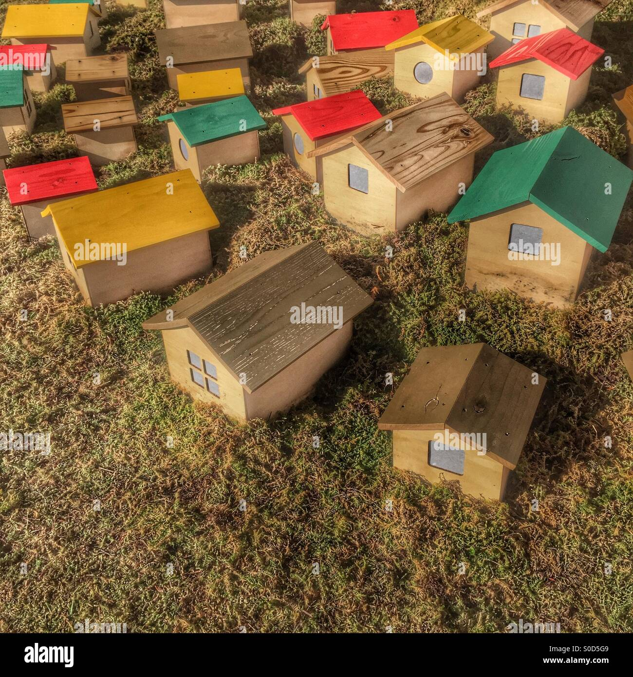 Miniature wooden houses with red, yellow, green and natural wood pattern roofs on grass lawn.Stock Photo
