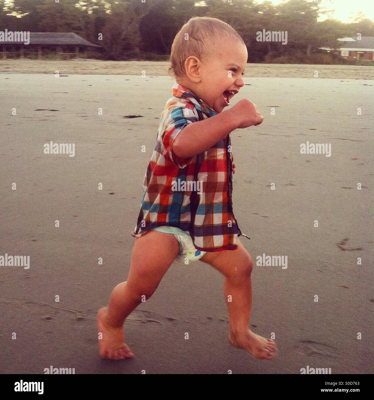 Toddler running on the beach - Stock Image