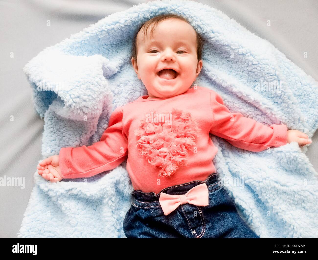 Happy smiling baby girl lying on blanket. She is wearing top with heart shape and blue jeans with bow tie. - Stock Image