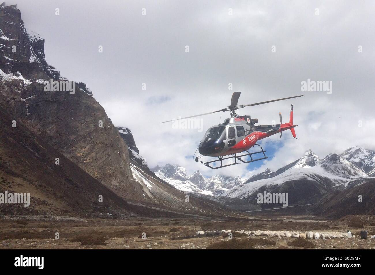 A rescue helicopter takes off from the village of Pheriche in the Everest region of Nepal. - Stock Image