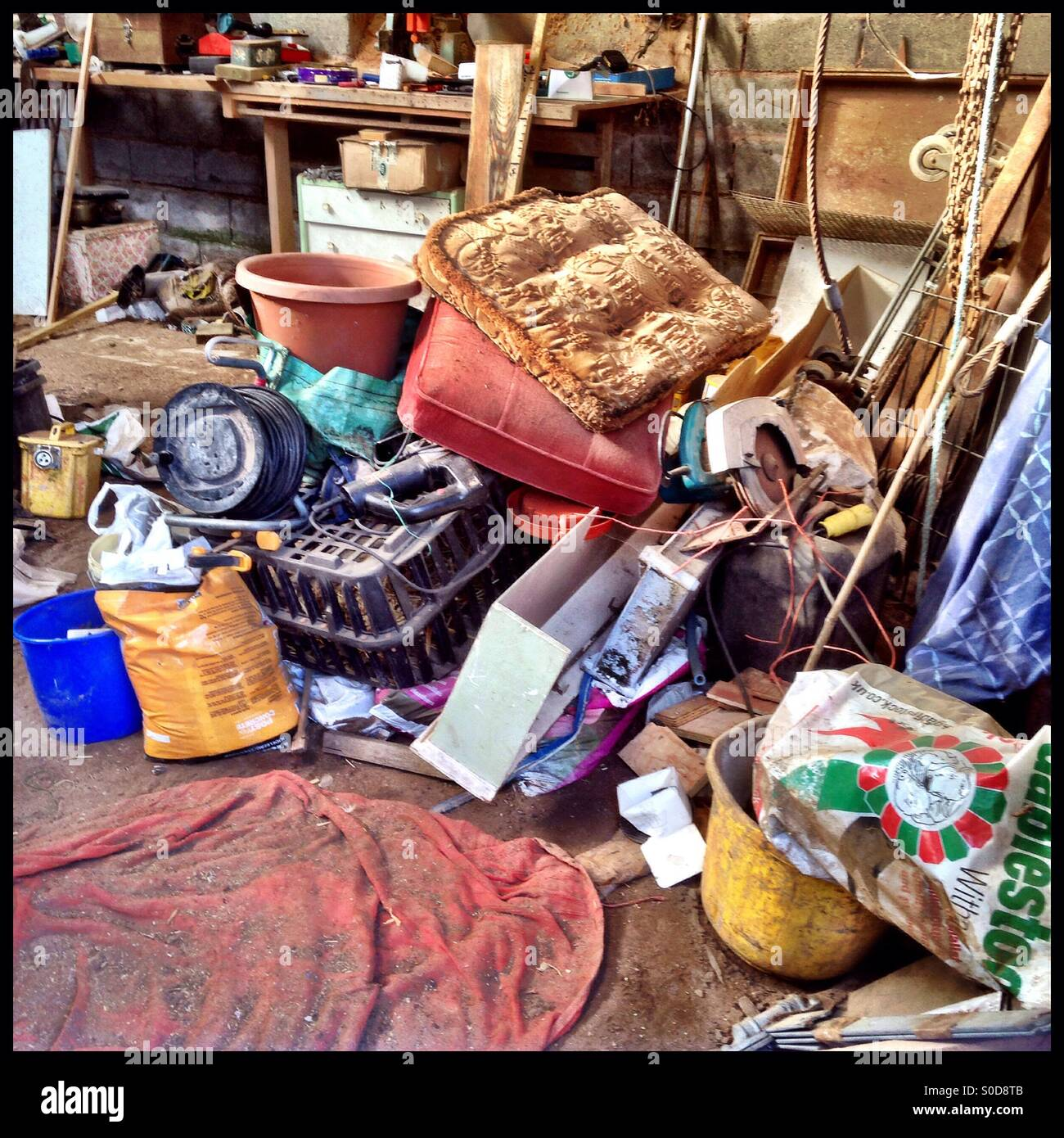 Pile of junk in large shed - Stock Image