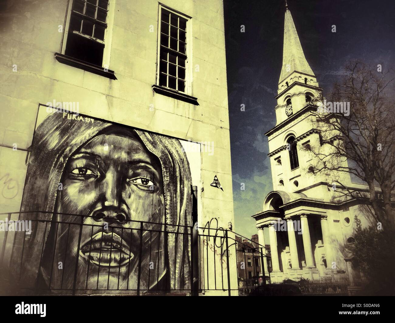 Street art by Portuguese artist Furia ACK with Christ Church Spitalfields in the background. Commercial Rd, Spitalfields, - Stock Image