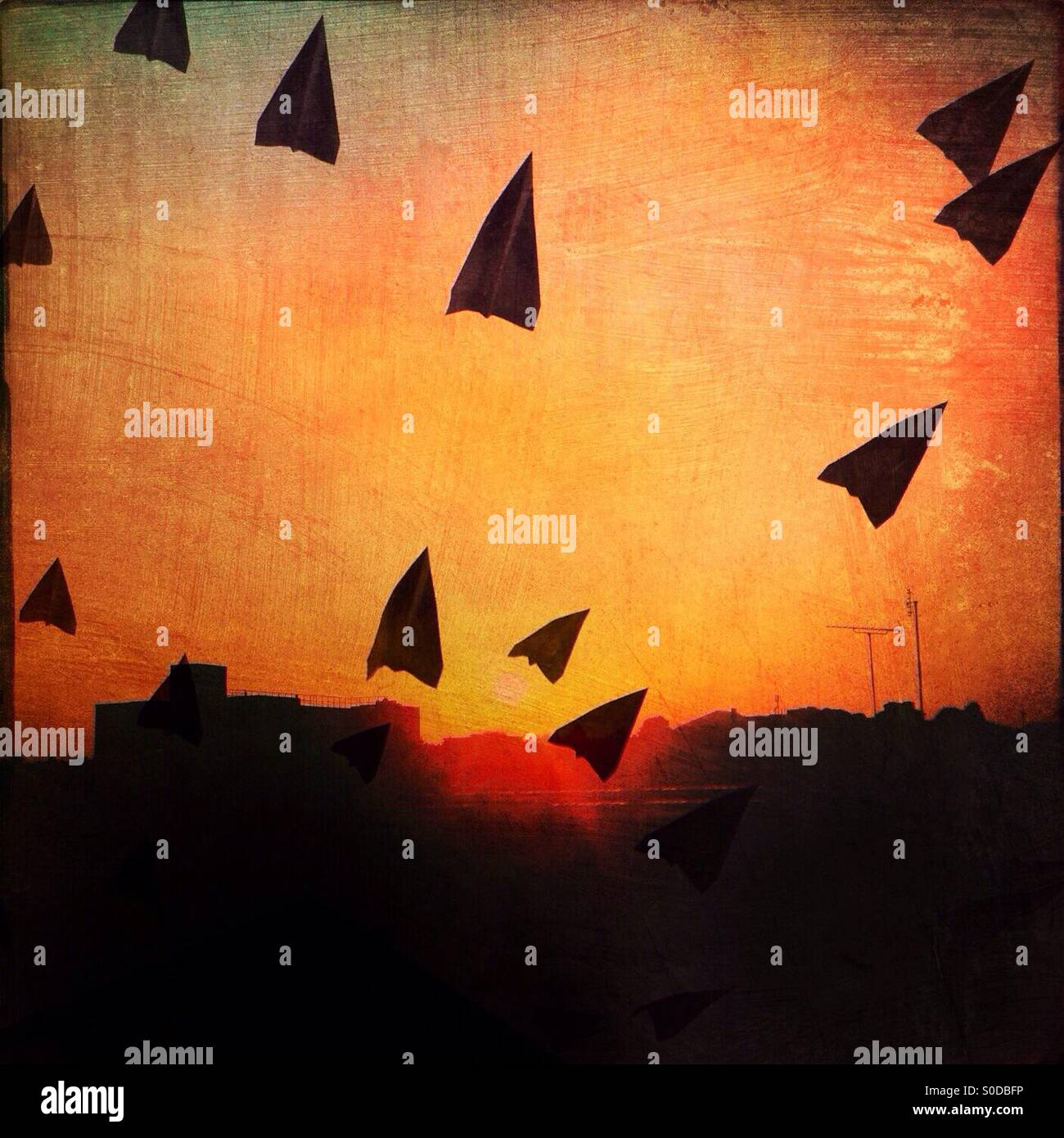 Conceptual photo of paper aeroplanes flying off into the distance against the backdrop of an urban skyline with - Stock Image