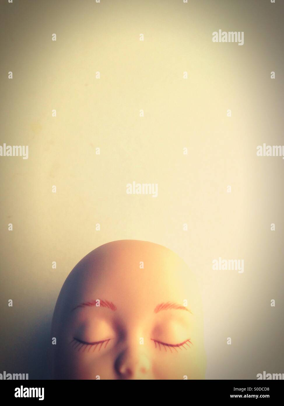 The top of a doll's bald head. - Stock Image