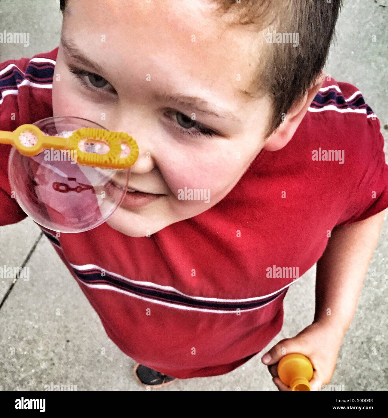 Boy holding a bubble wand with a dripping soap bubble - Stock Image