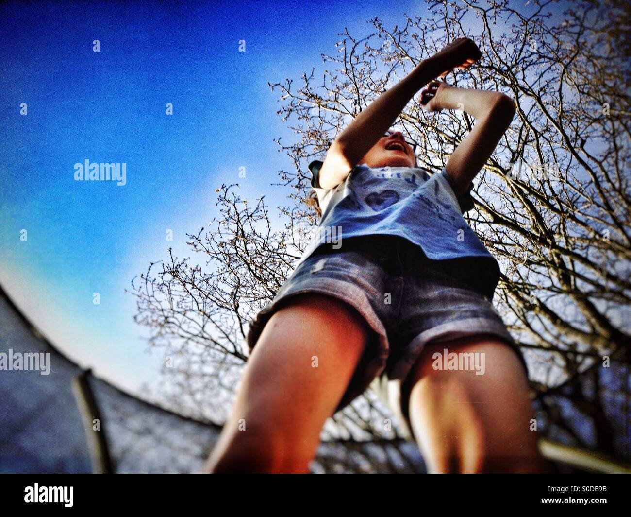 Young girl bouncing on trampoline - Stock Image
