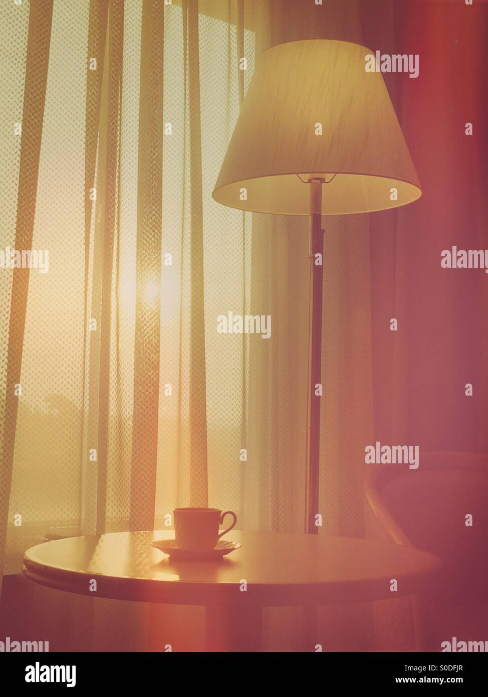 Hotel room sunrise scene featuring coffee cup, table, floor lamp, chair and curtains with vintage bokeh overlay. Stock Photo