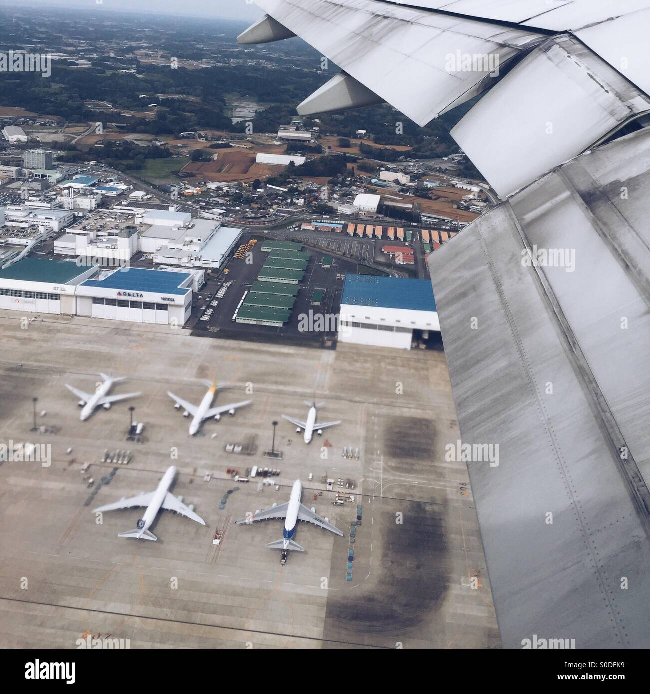 Aerial view of airplane wing, warehouses and airplanes on the ground at Narita International Airport in Chiba Prefecture, Stock Photo