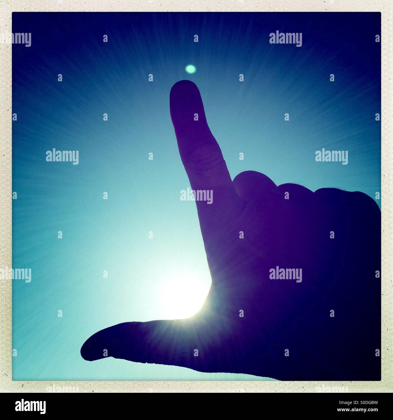 Silhouette of thumb and index finger pointing towards sun - Stock Image