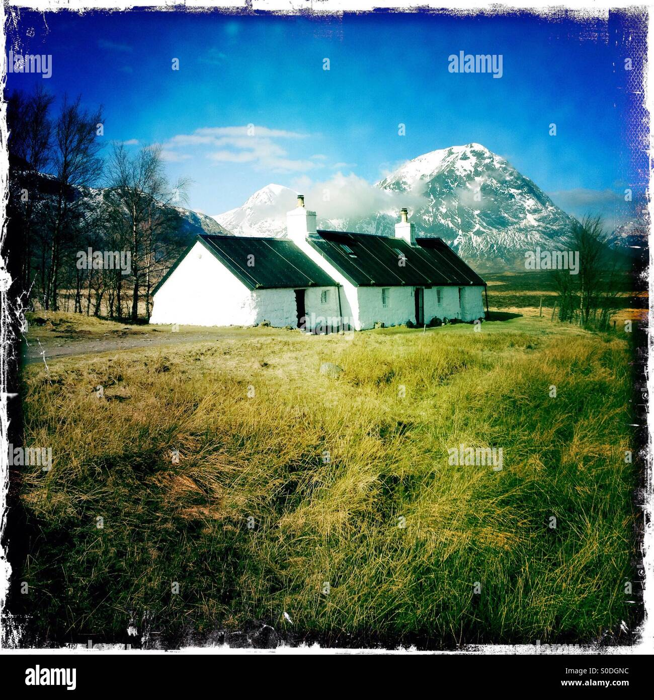 Historic white cottage with mountain snow capped behind, Glencoe Scotland - Stock Image