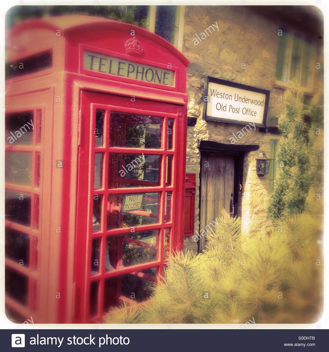 Old style red telephone kiosk, not in use, in the garden of Weston Underwood Old Post Office. - Stock Image