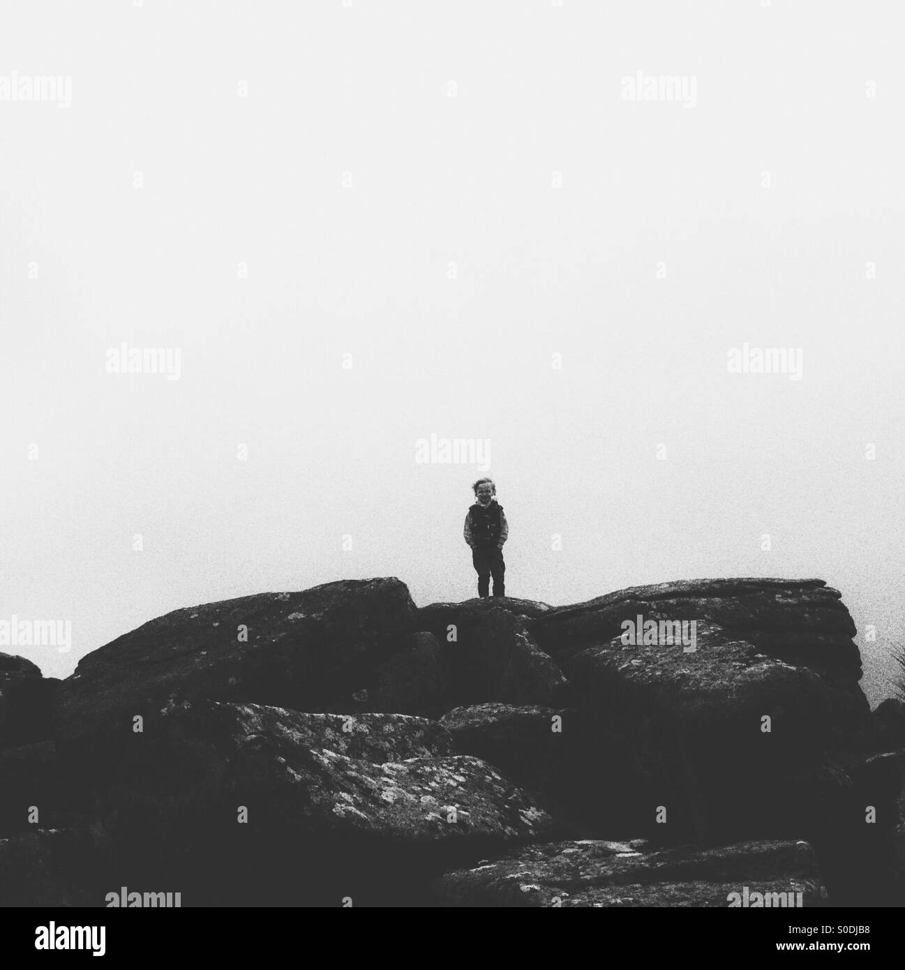 Young boy alone on a tor on Dartmoor - Stock Image