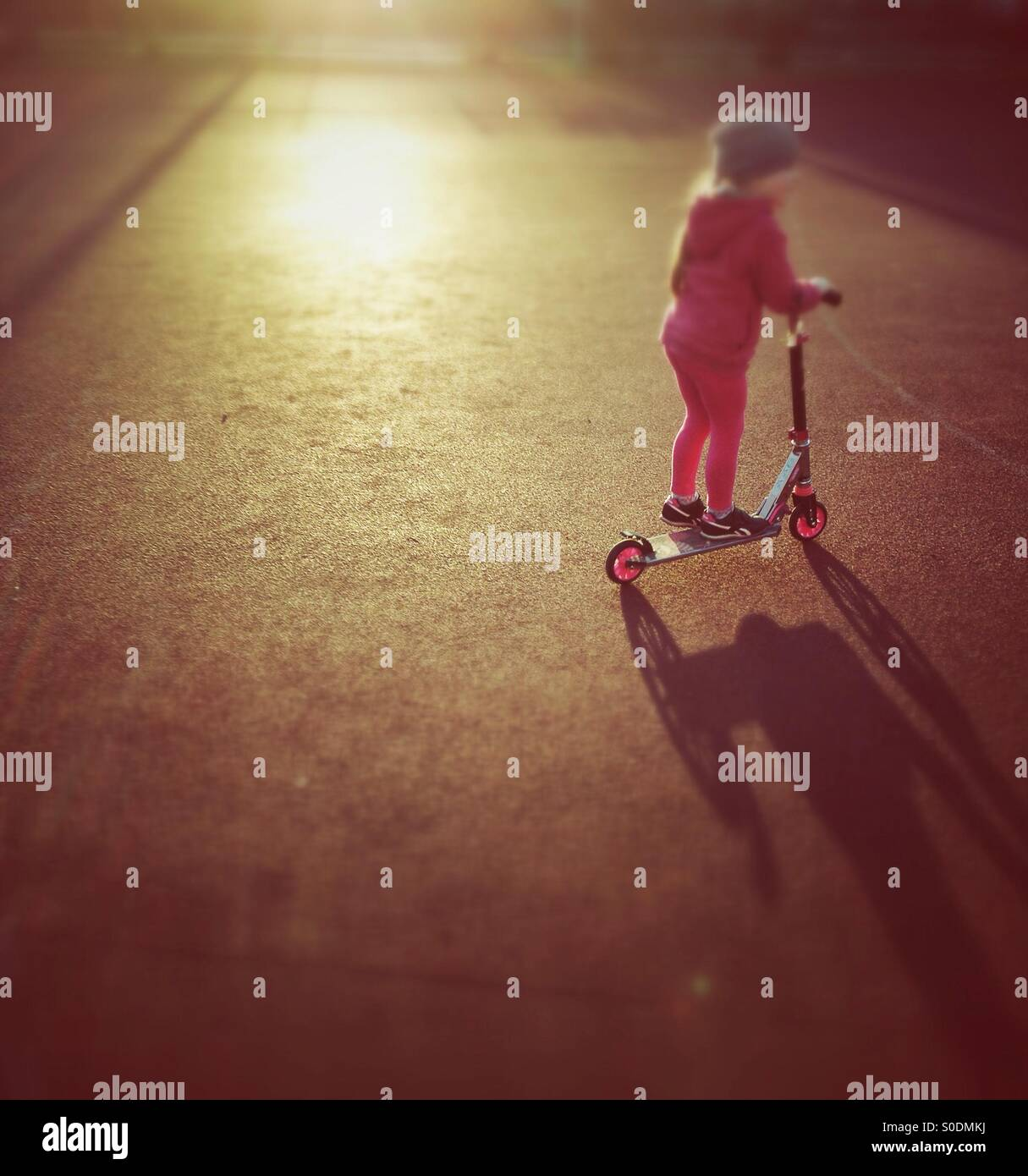 Child riding scooter - Stock Image