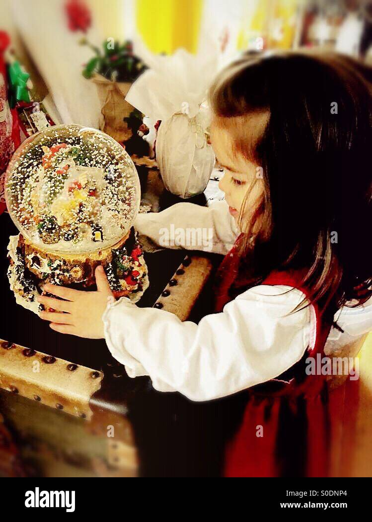 Little girl looking into a snow globe on Christmas morning Stock Photo