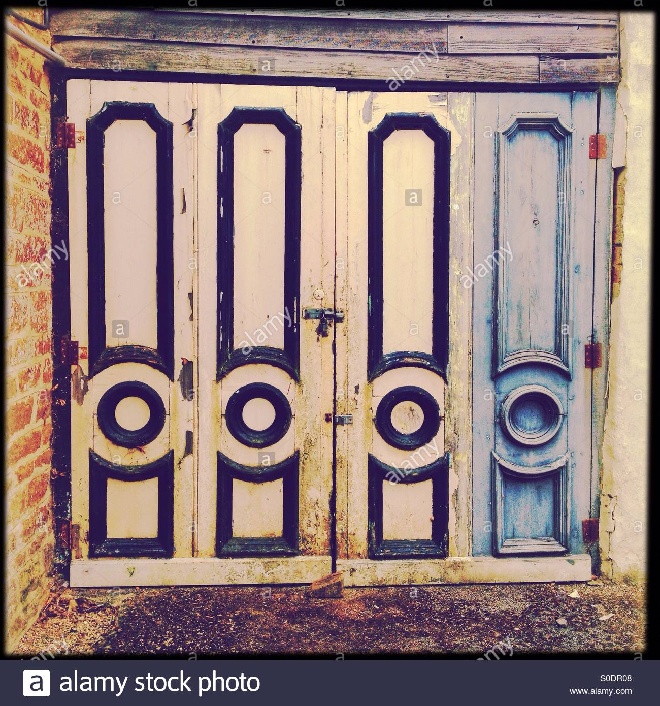 Dilapidated garage doors sporting an unusual design - Stock Image