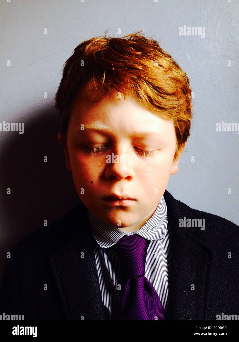 Ginger haired boy with eyes closed - Stock Image