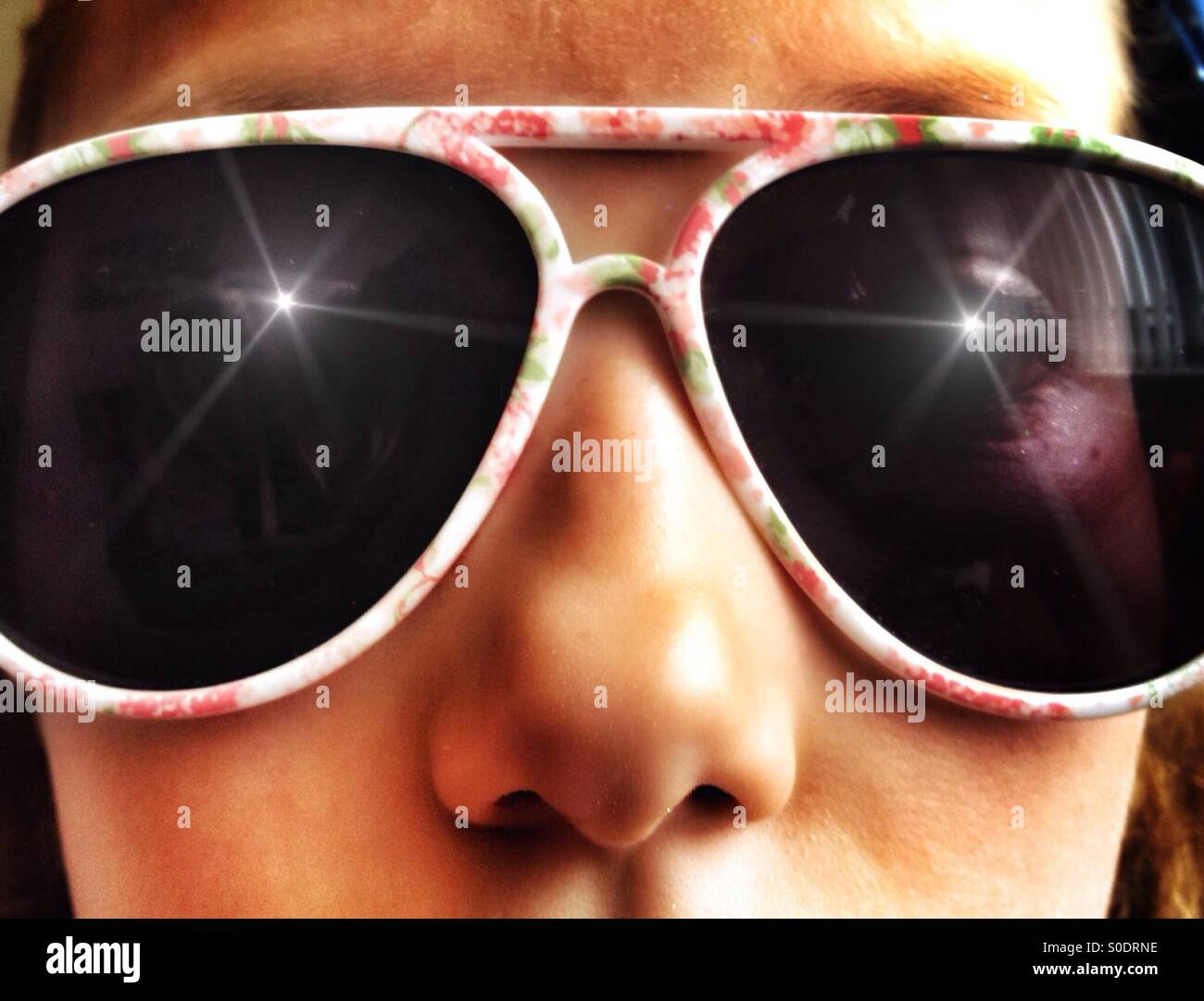 Young girl wearing dark sunglasses - Stock Image
