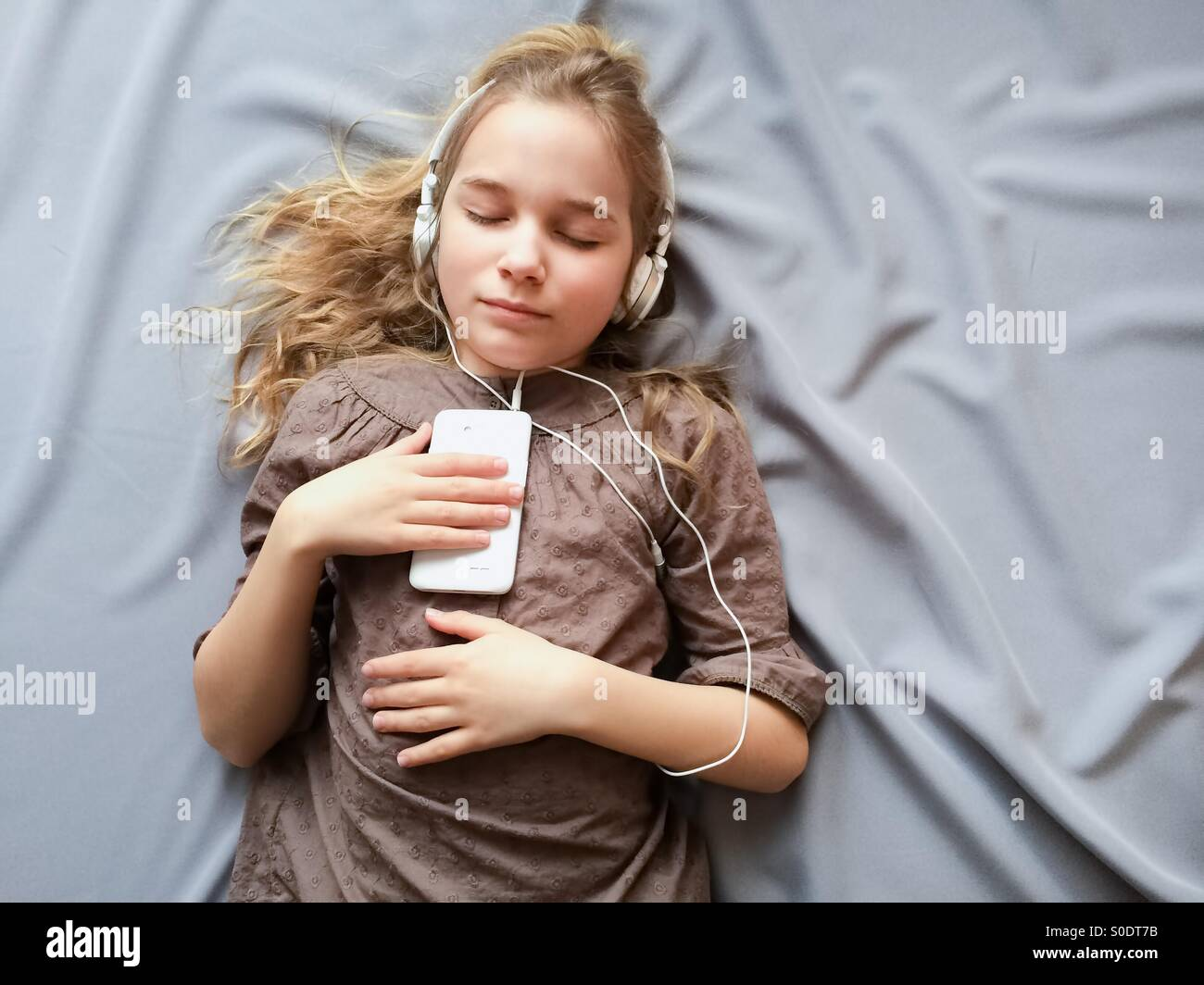 It sounds like a dream. Young girl lying on the bed and dreaming about something with closed eyes. - Stock Image