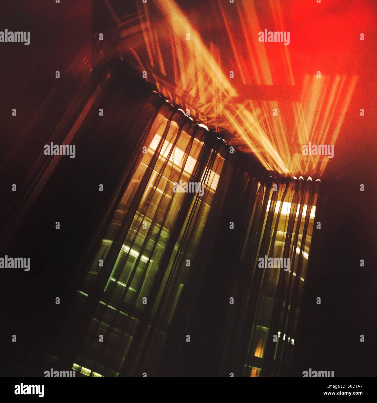 An abstract image of two tall windows with multicolor lights streaming through. - Stock Image