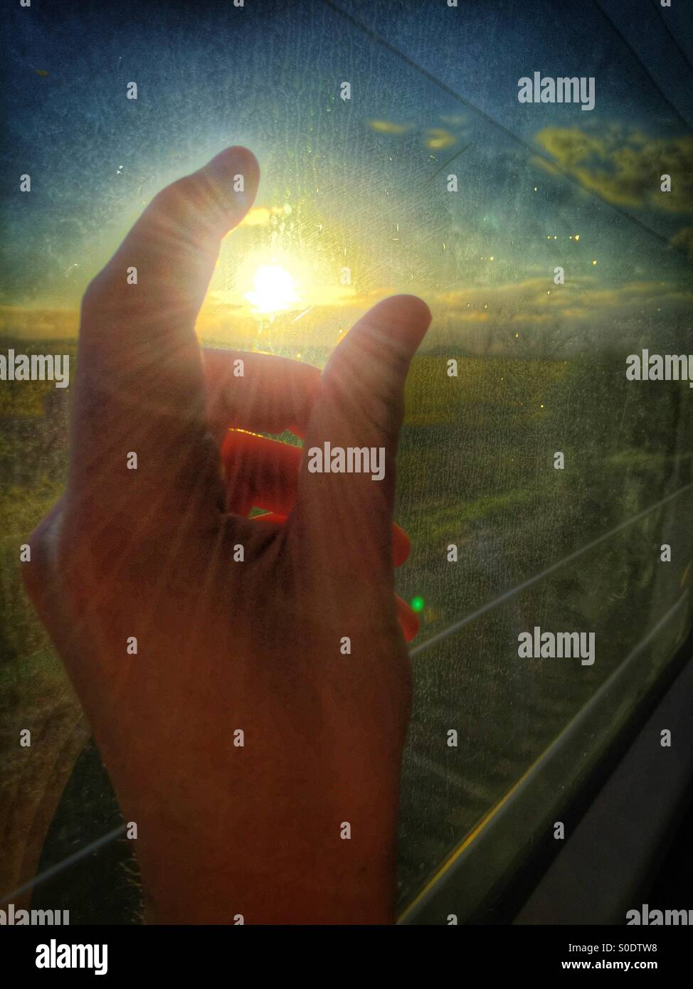 Hand grabbing the sun - Stock Image