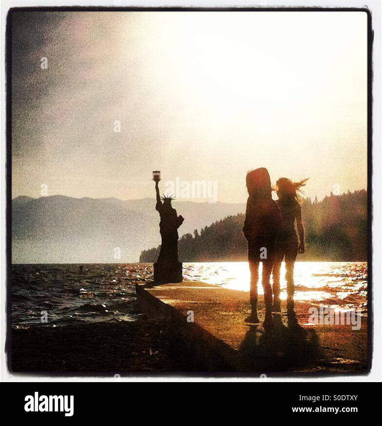 Two children stand next to the replica of the Statue of Liberty in Sandpoint, Idaho. - Stock Image