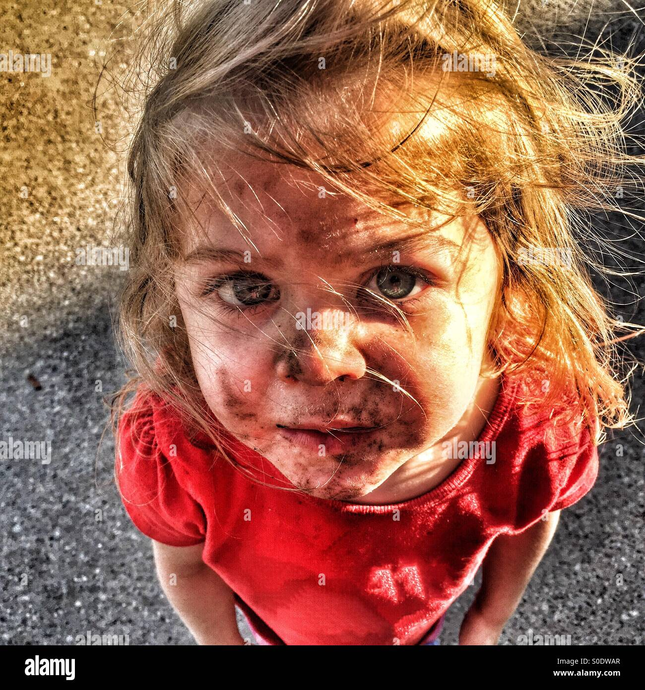 Child with a dirty face and windswept hair looking up - Stock Image