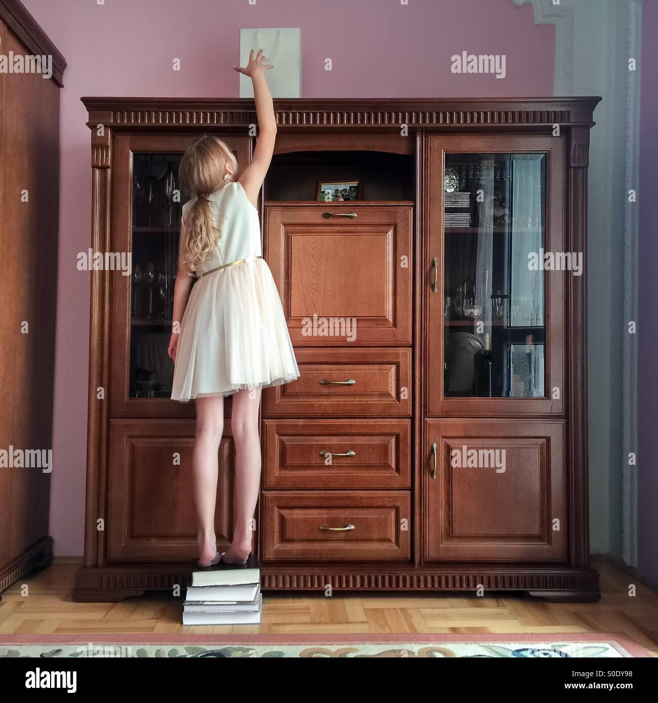 Young girl reaching the bag with a gift put high on the cupboard - Stock Image