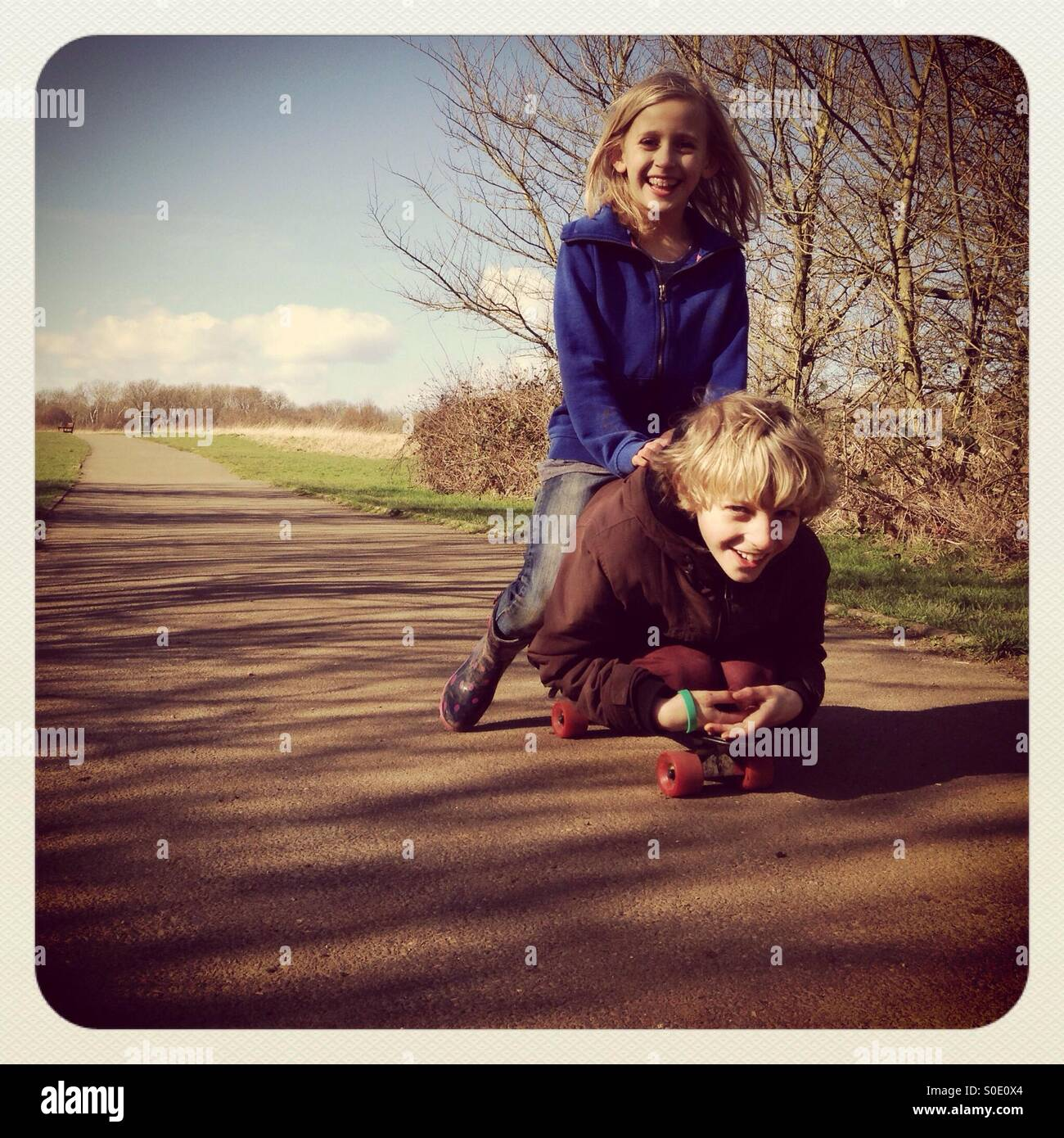 Brother and sister on skateboard - Stock Image