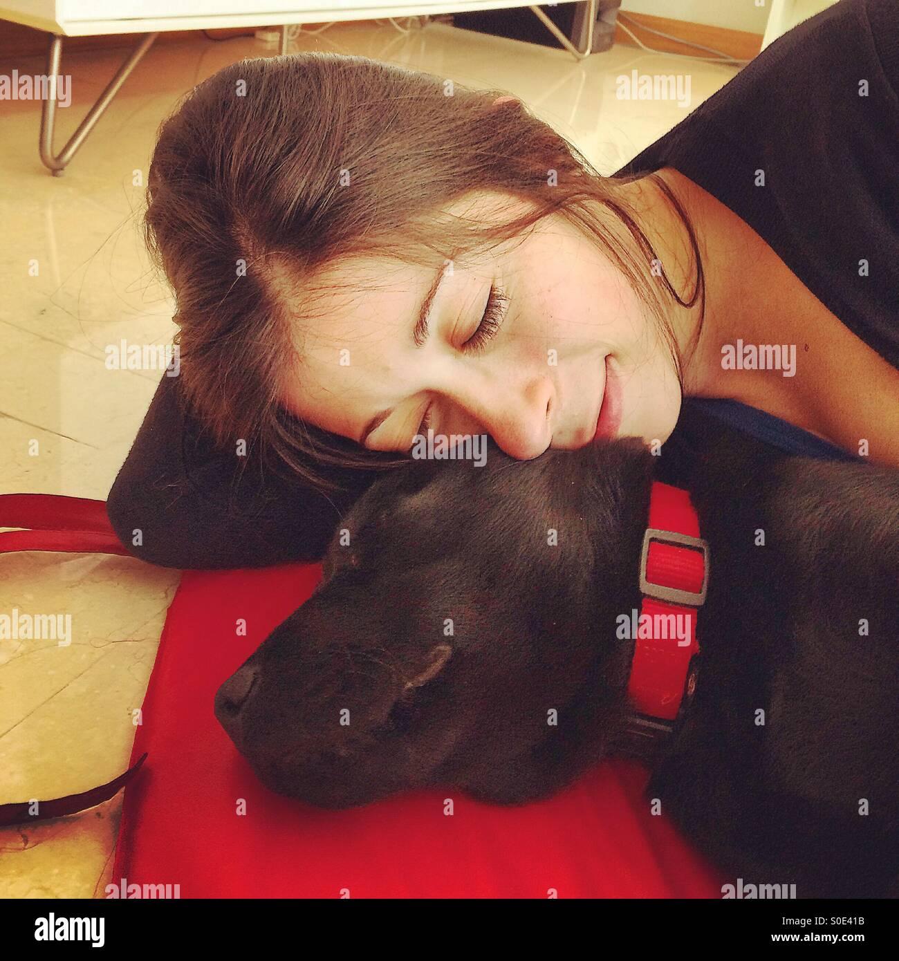 Young woman sleeping next to black Labrador Retriever puppy - Stock Image