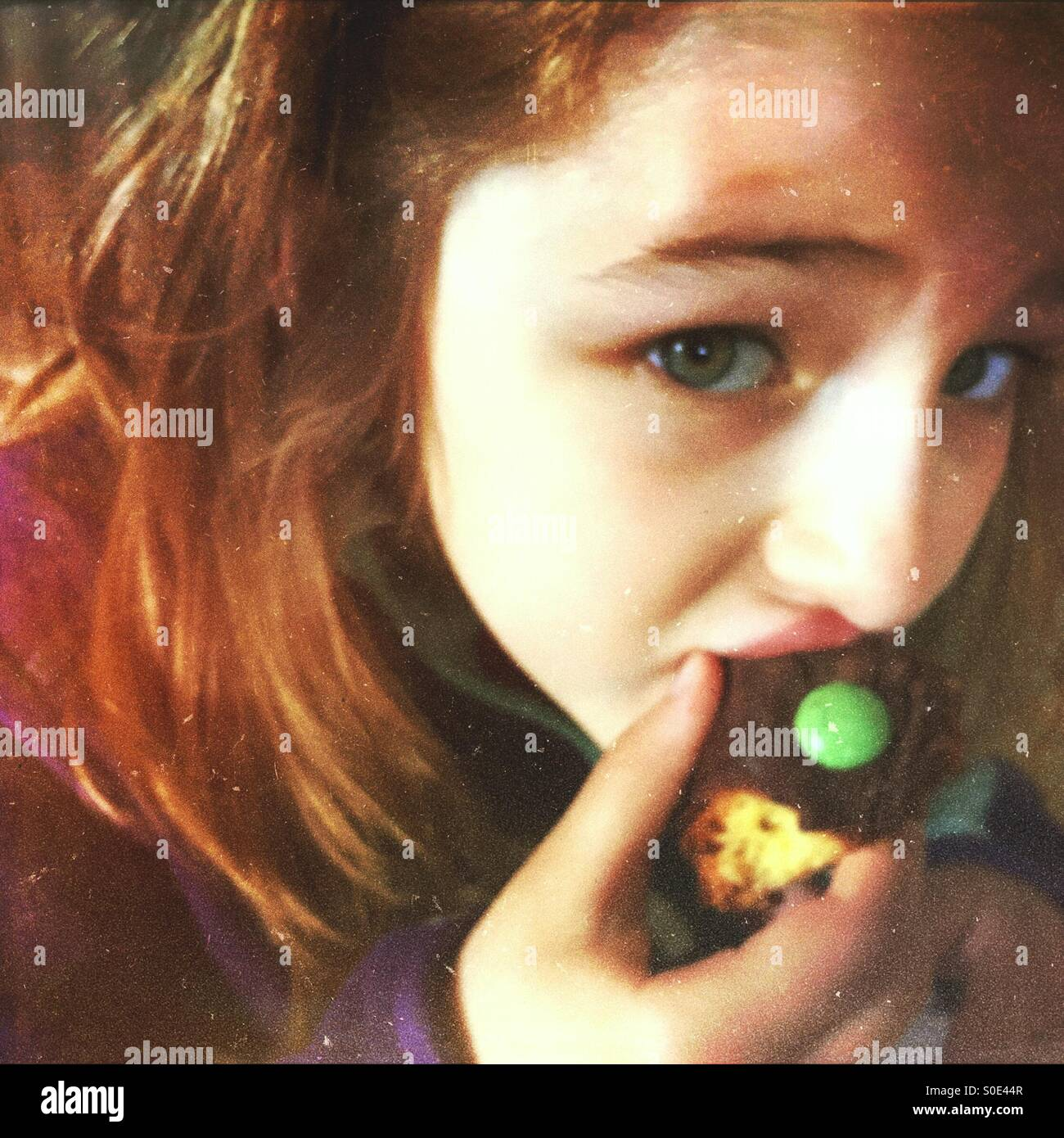 Caught red handed. Sneaky little girl eating chocolate cake. - Stock Image