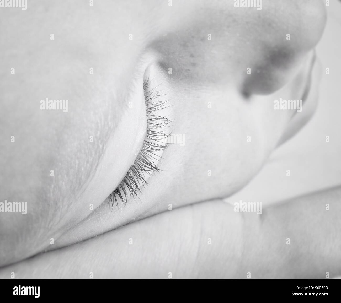 Young girl asleep resting on her hand - Stock Image
