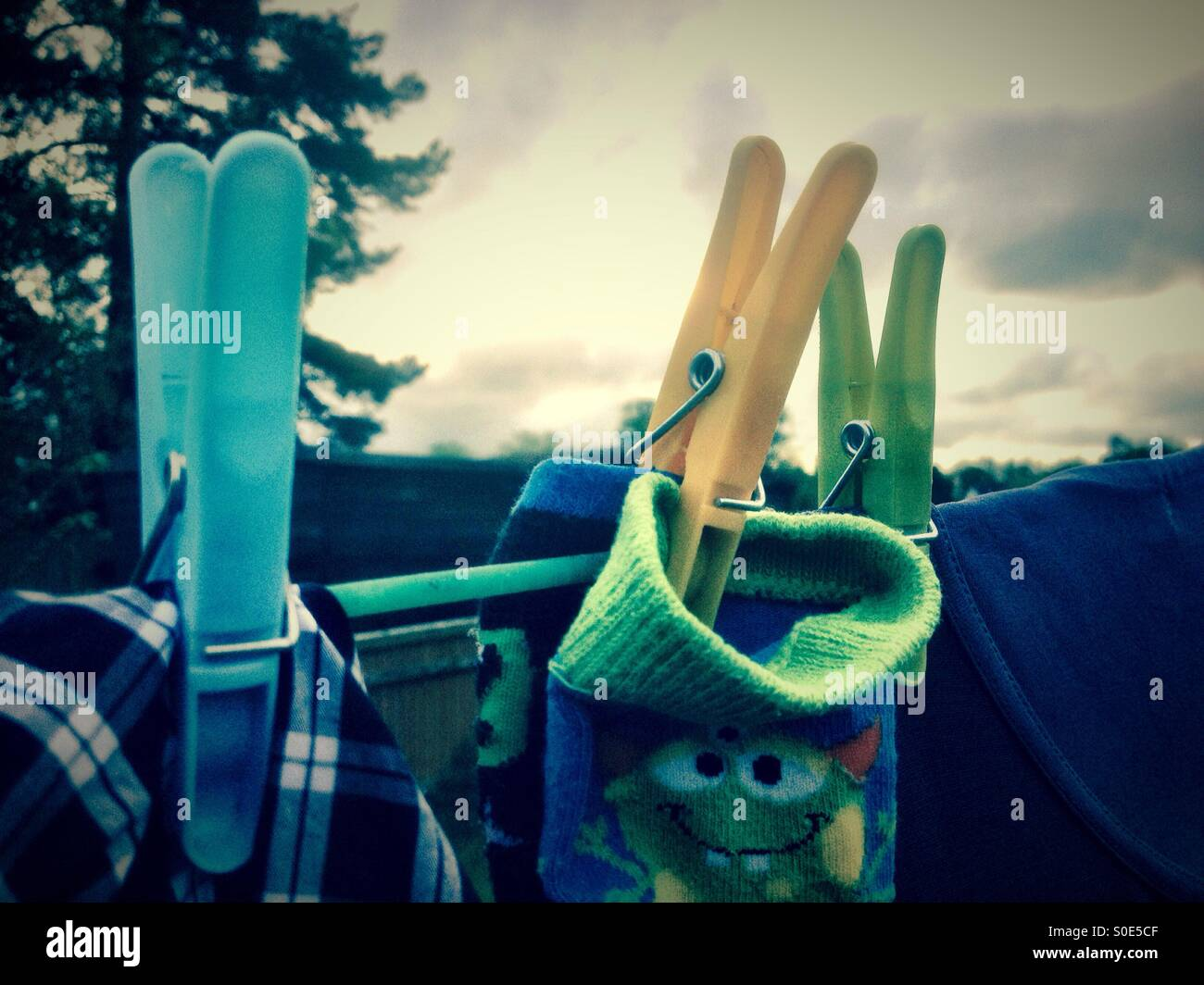 Close up of pegs holding clothes on a washing line. Stock Photo