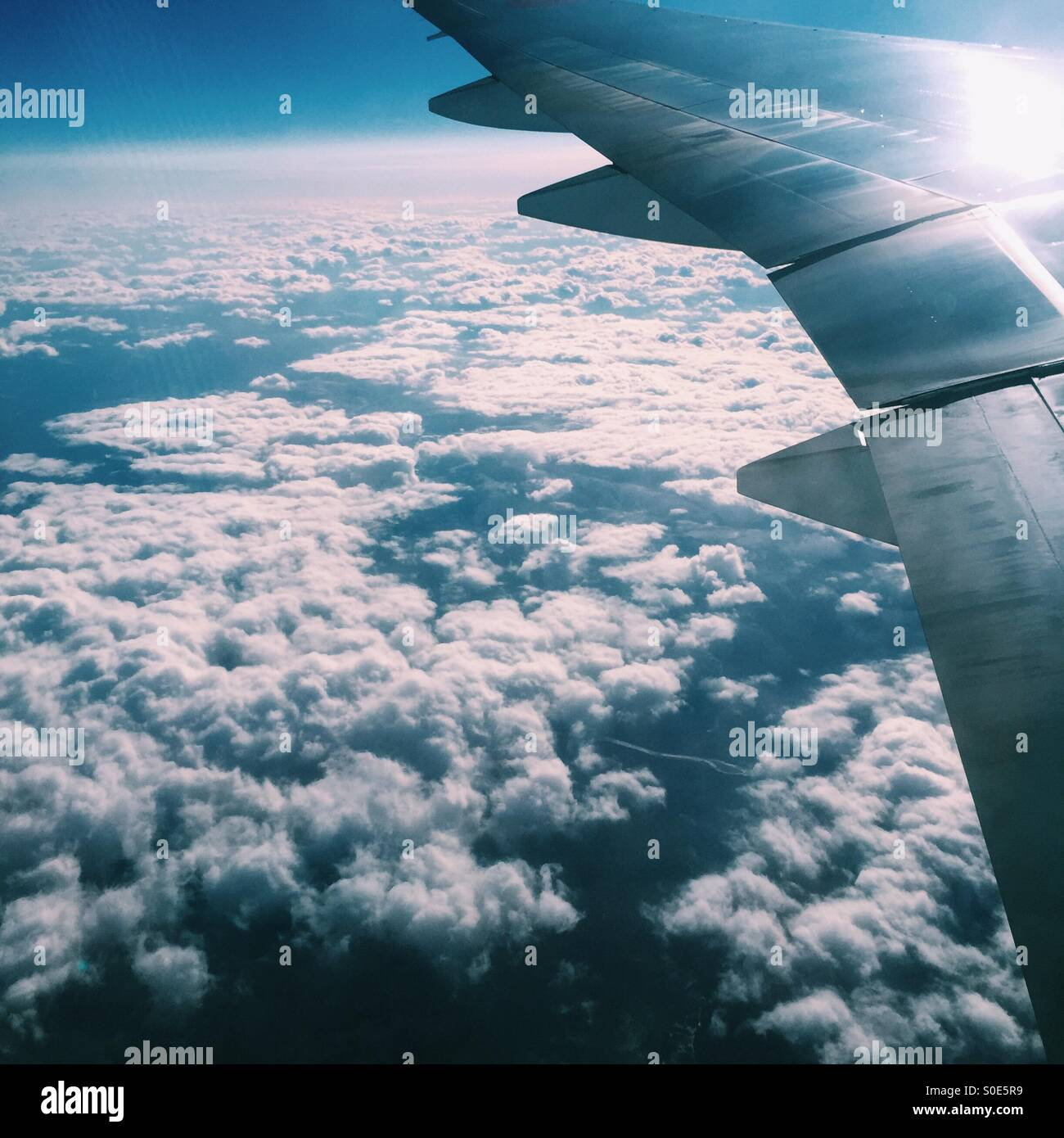 Aerial view of airplane wing and clouds as seen from window of airplane. Stock Photo